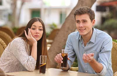 یک دختر و یک پسر جوان پشت یک میز در خیابان نشستهاند. دختر با موهای بلند و قیافه ناراحت دستش را زیر چانهاش گذاشته و پسر در حالی که لبخند میزند و دستانش را تکان میدهد، صحبت میکند.