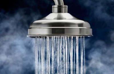 تصویر یک دوش آب استیل در حالی که از آن آب داغ خارج میشود