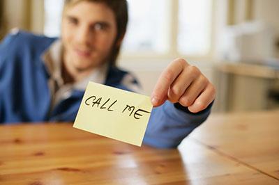 تصویر یک مرد در پس زمینه در حالی که کاغذ یادداشت در دستش را رو به دوربین گرفته است