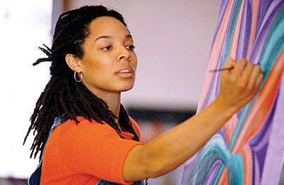 زن با پوست تیره و موهای مشکی و بلند در حال کشیدن نقاشی