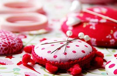 آهنرباهای کوچک فانتزی با رنگ سفید با خال خالهای قرمز و قرمز گلدار در حالی که سوزنها رویشان چسبیدهاند