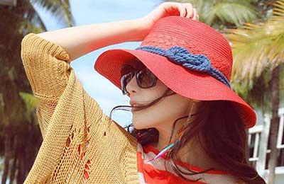 دختر زیبا با کلاه قرمز با نواری آبی و عینک آفتابی در حالی که دست خود را روی کلاهش گذاشته به دوردست خیره شده