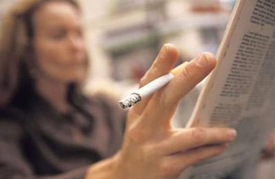 زن میانسال در حالی که یک سیگار بین انگشتان خود دارد در حال روزنامه خواندن