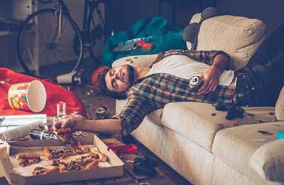 یک پسر جوان در حالی که اطرافش به هم ریخته و نامرتب است روی کاناپه خوابیده در حالی که در دست راست خود یک برش پیتزا و در دست چپش یک قوطی نوشابه است