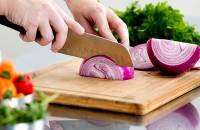 دستانی در حال خرد کردن پیاز با یک چاقوی پهن روی یک تخته آشپزی