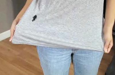 زنی با تی شرت طوسی و شلوار جین در حال نشان دادن که جوهر روی تیشرتش