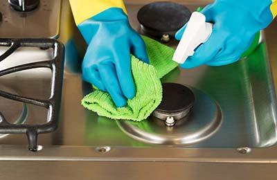 دستانی با دستکشهای دو رنگ آبی و زرد در حال اسپری کردن روی سطح گاز و پاک کردن آن با یک دستمال سبز
