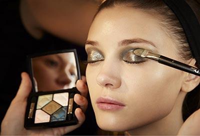 زن جوان در حال زدن سایه چشم بر روی پلک هایش