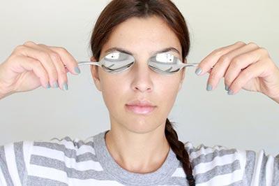 یک زن جوان با موهای بافته شده و لباس راه راه سفید و طوسی دو قاشق استیل را روی چشمان خود با دستانش نگه داشته