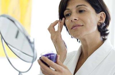 زن میانسال با موهای کوتاه قهوهای با حوله سفید در حالی که در آینه خود را میبیند در حال زدن مرطوبکننده به صورت خود است