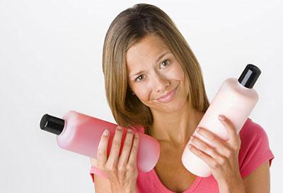 زن در حالی که نرم کننده مو در دستانش دارد