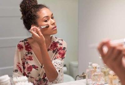 زن روبروی آینه در حال آرایش کردن