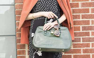 زن در حالی که عینک آفتابی و کیف در دست دارد