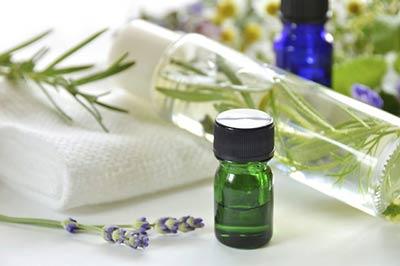 یک ساقه و یک عدد گل رزماری در کنار یک شیشه کوچک سبز و یک شیشه کوچک آبی زنگاری حاوی اسانس رزماری