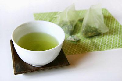 دو کیسه چای سبز بر روی یک دستمال سبز رنگ در کنار یک کاسه کوچک سفید حاوی مقداری چای سبز