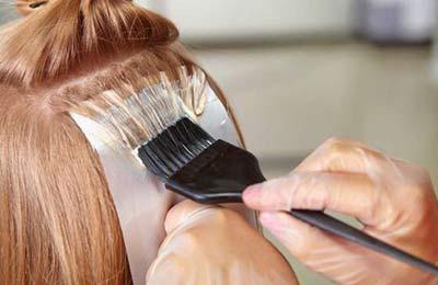 زنی با دستکش در حال رنگ کردن مو با استفاده از یک فرجه سیاه و فویل