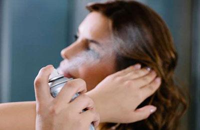 دستان زنی در حال اسپری شامپوی خشک بر روی موهای زن دیگر