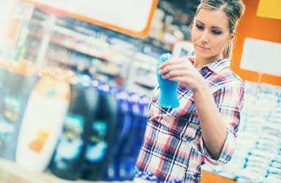 زن با لباس چهارخانه در فروشگاه با یک قوطی آبی رنگ شامپو در دست