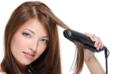 زنی در حال کشیدن اتوی مو