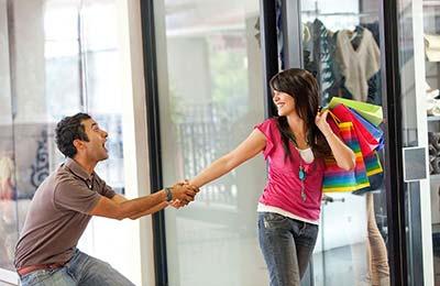 تصویر یک زن و یک مرد جوان در حالی که زن ساکهای خریدش را با دست روی شانهاش گذاشته و میخندد و مرد دست زن را گرفته و میکشد تا مانع رفتن او داخل مغازه شود