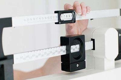 دست یک زن در حال تنظیم ترازوی وزن کشی