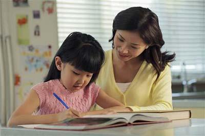 مادر با لباس زرد در حال آموزش به دختر کوچکش با لباس صورتی