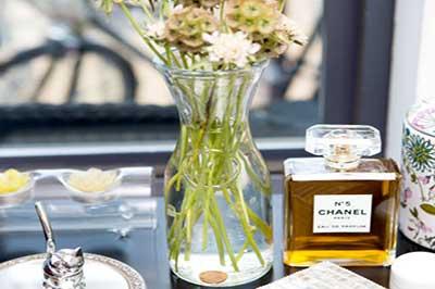 گلدان با یک سکه درون آن وشیشه عطر روی میز