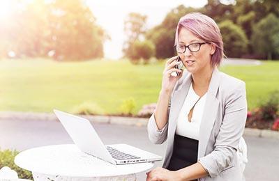 زن در حال صحبت کردن با تلفن در حیاط خانه