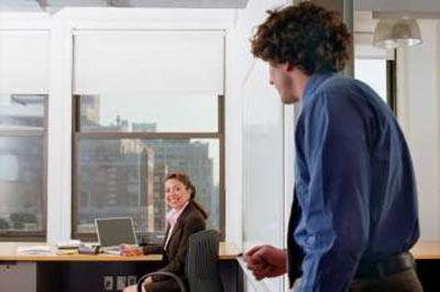 مردی با پیراهن آبی و شلوار قهوه ای و موهای قهوه ای مجعد در حال ورود به اتاق زنی که نشسته و لبخند میزند و کت و دامن قهوه ای به تن دارد