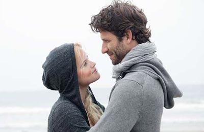 زن با سوییت شرت خاکستری در حال نگاه کردن به مردی با ژاکت طوسی و شال طوسی با ریش و موهای نامرتب