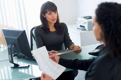 زنی با موهای تیره با لباس راه راه با یک پرونده در دست در حال حرف زدن با زنی با موهای بلند مجعد که کاغذی در دست دارد