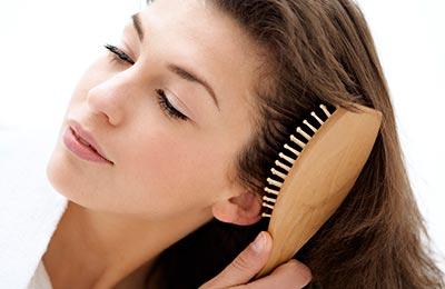 زنی با موهای قهوهای در حال برس کشیدن موها با یک برس پارویی بژ