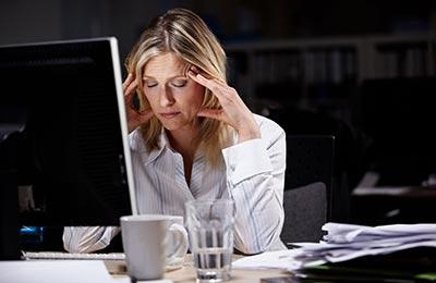 زن میانسال در حالیکه پشت کامپیوتر نشسته و چشمانش را بسته و دستانش را کنار شقیقههایش گذاشته است