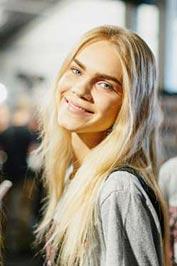 دختری جوان با پوستی روشن و موهایی بلوند طلایی در حال لبخند زدن