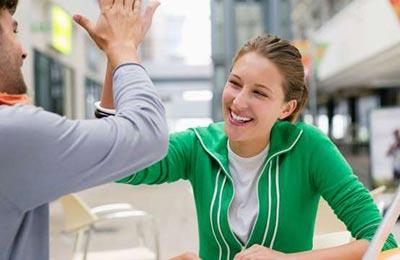 زن و مرد در حالی که پشت میزی در خیابن نشستهاند لبخند میزنند و دستهایشان را به یکدیگر می زنند