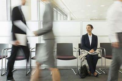 زنی با کت و شلوار تیره و پیراهن سفید در حالی که روی صندلی نشسته به اطراف نگاه می کند