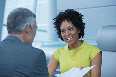 زنی با لباس زردرنگ و موهای کوتاه مجعد در حال لبخند زدن روبروی مردی میانسال نشسته است