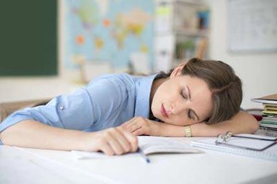 زن با لباس آبی بر روی کاغذها خوابش برده