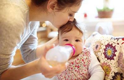 کودکی زیبا با لباس گل گلی در حال شیر خوردن با شیشه از دستان یک زن که در حال بوسیدن اوست