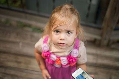 دختر خردسال زیبا با یک موبایل در دستش به بالا نگاه میکند