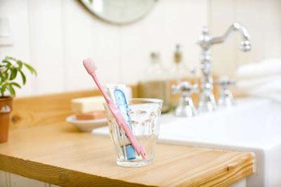 یک مسواک صورتی و یک خمیردندان آبی داخل یک لیوان شیشهای در کنار سینک دستشویی