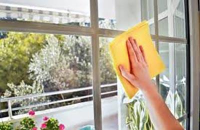 دست زنی که با دستمال زردی شیشههای تراس را پاک میکند