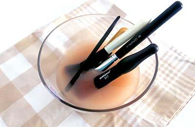 چهار عدد برس آرایشی در اندازههای مختلف درون مایعی در یک کاسه شیشهای