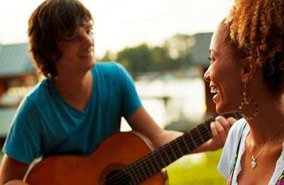 زن با پوست تیره و موهای قهوهای در حالی که لبخند میزند به پسر که در حال گیتار زدن و خواندن است نگاه میکند