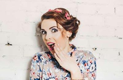 یک زن با موهای قهوهای روشن با دهان باز و چشمان گشاد کرده دستش را جلوی دهان خود گرفته و به دوربین نگاه میکند