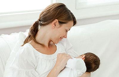 یک زن با موهای بلند و مشکی که از پشت سر بسته شده در حال شیر دادن به نوزادش