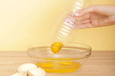یک دست در حالیکه بایک قوطی پلاستیکی یک زرده تخم مرغ را از داخل یک کاسه پیرکس بیرون می آورد