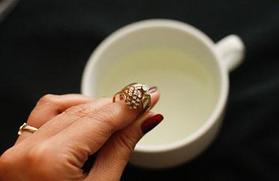 یک دست با یک انگشتر داخل انگشتش و یک فنجان سفید رنگ