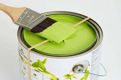 یک قوطی رنگ دسته دار سفید رنگ حاوی رنگ سبز مغز پسته ای با یک قلم مو با دسته چوبی بر روی آن