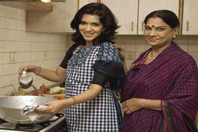 زن جوان هندی با لباس سنتی هند در حال آشپزی در آشپزخانه در کنار زن مسن هندی با ساری بنفش